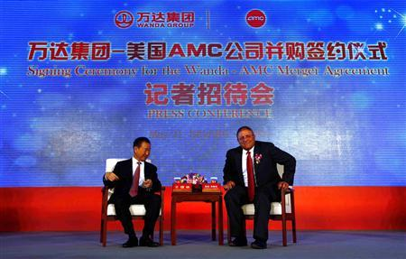 AMC Entertainment CEO Lopez sits next to Wanda Group President Wang before a media conference in Beijing